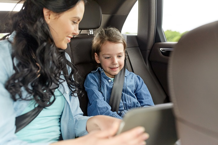 mom and child playing in rear seat of car